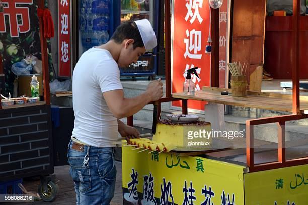 Guy cutting cake in the muslim quarter of Xi'an, Shaanxi
