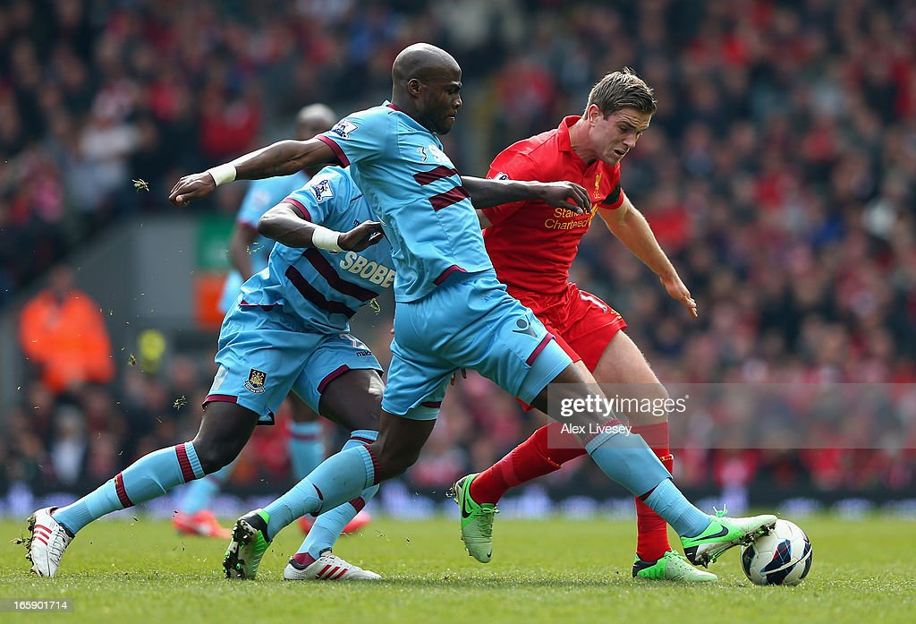Guy Demel of West Ham United challenges Jordan Henderson of Liverpool during the Barclays Premier League match between Liverpool and West Ham United at Anfield on April 7, 2013 in Liverpool, England.