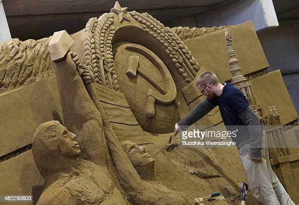 Guy Deveau of Canada finishes a sand sculpture named 'Soviet Union' at the Sand Museum in the Tottori Dune on April 3 2014 in Tottori Japan The 7th...