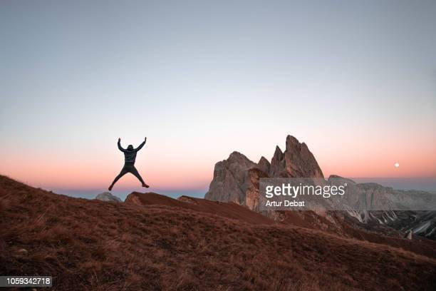 guy discovering the beautiful dolomites mountains on the top of the seceda mountains at dusk. - cartography stock photos and pictures