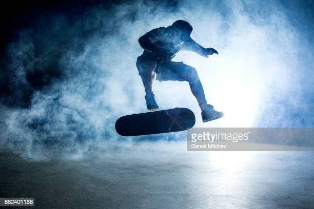 Guy doing a trick on a skateboard with smoke around him.