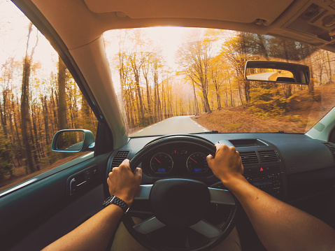 Guy driving car from personal perspective in a beautiful mountain road between forest with autumn colors in the Montseny nature reserve close to Barcelona city during day trip. - gettyimageskorea