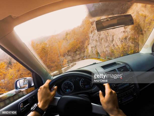 guy driving car from personal perspective in a beautiful mountain road between forest with autumn colors in the montseny nature reserve close to barcelona city during day trip. - volant de voiture photos et images de collection