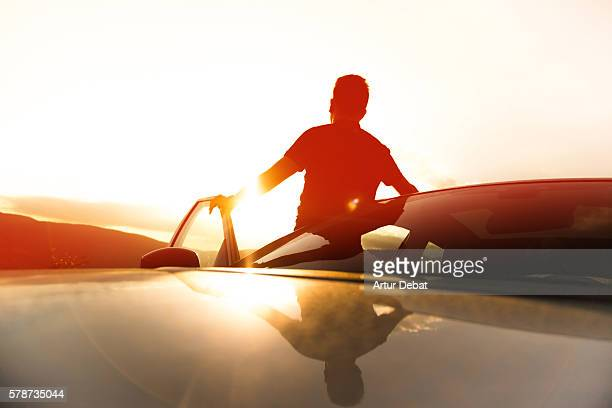 Guy during a road trip with suv car in the Catalan Pyrenees on summertime with beautiful sunset light and golden mountains.