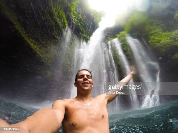 Guy during travel vacations enjoy swim under the stunning waterfall with wild nature in Indonesia taken selfie with action cam.