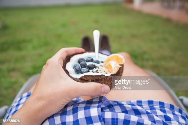 Guy eating healthy breakfast food in the morning in home garden inside coconut with yogurt, fruit and cereals taken directly from above.