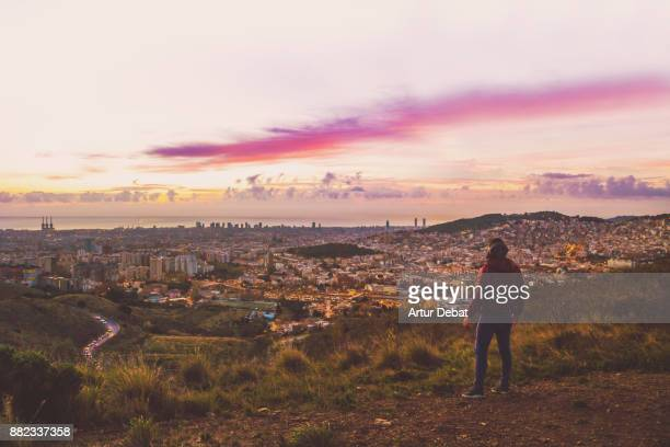 guy enjoying sunrise over barcelona city from cool viewpoint with unique perspective of the city, facing the city and contemplating the view alone from in the collserola mountains. - look back at early colour photography stock photos and pictures