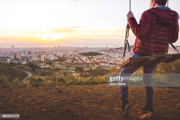 Guy enjoying sunrise over Barcelona city from cool viewpoint with unique perspective of the city, sitting on swing relaxing and contemplating the view from lonely tree in the Collserola mountains.
