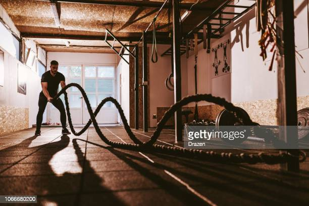 guy exercising in the cross training facility - crossfit stock pictures, royalty-free photos & images