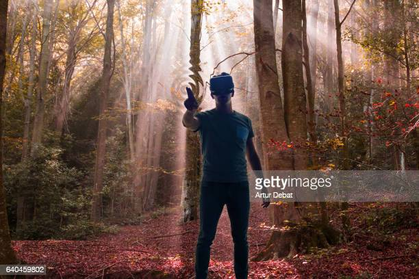 Guy experiencing the virtual reality headsets immerse in another dimension touching and feeling the trees dimension scenario transported in a beautiful nature forest.