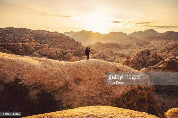 guy exploring the beautiful rock formations of petra during sunset. - jordan middle east stock pictures, royalty-free photos & images