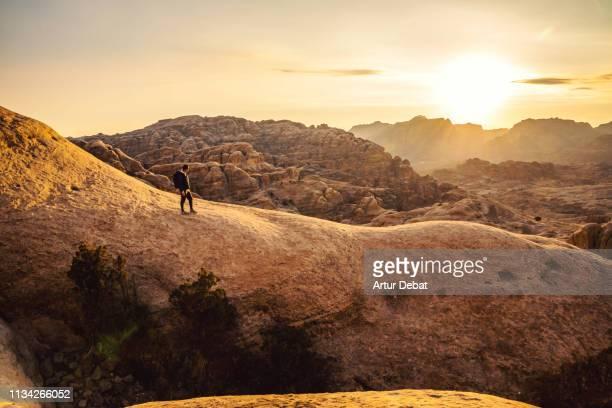 guy exploring the beautiful rock formations of petra during sunset. - paisajes de jordania fotografías e imágenes de stock