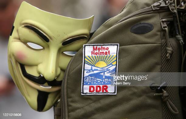 """Guy Fawkes mask, used by the Anonymous movement, is seen next to a patch reading """"My Homeland, the GDR,"""" or the former East Germany, on the backpack..."""