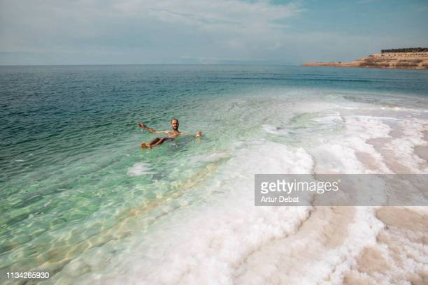 guy floating in the dead sea during vacations with amazing sea colors. - dead sea stock pictures, royalty-free photos & images