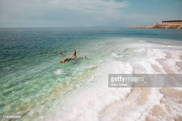 guy floating in the dead sea during vacations with amazing sea colors. - mar muerto fotografías e imágenes de stock