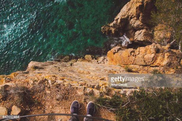 Guy from personal perspective looking down from cliff in the Costa Brava.
