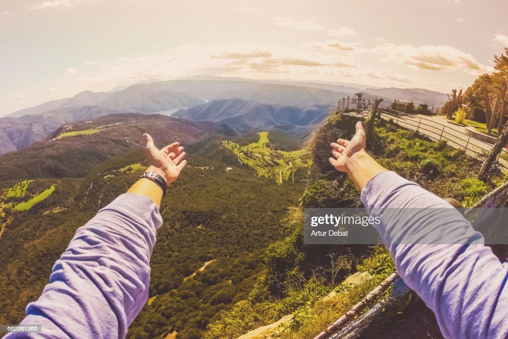 Guy from personal perspective showing with hands the amazing landscape view from the top of mountain viewpoint in the Collsacabra mountains in the Catalonia region during a hike adventure trip in the zone. : Stock Photo