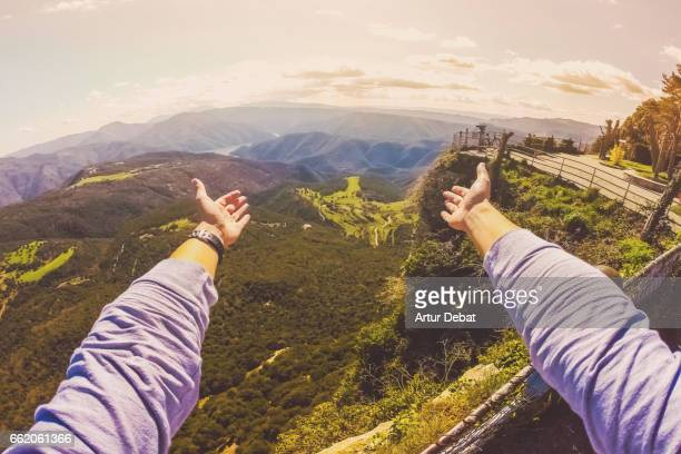 Guy from personal perspective showing with hands the amazing landscape view from the top of mountain viewpoint in the Collsacabra mountains in the Catalonia region during a hike adventure trip in the zone.