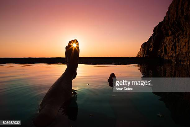 Guy from personal perspective swimming in a natural pool in the Mediterranean Sea Costa Brava shoreline watching the sunrise with his feet floating into the water during summer time.