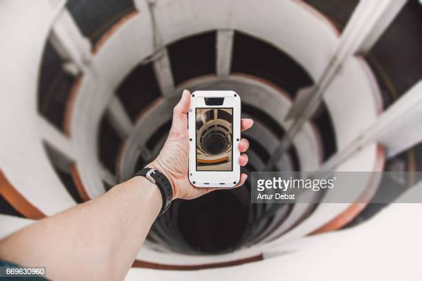 guy from personal perspective taking a picture with smartphone of a beautiful spiral geometric shape created by a parking ramp in a decay architecture building with nice vanishing point and vertigo feeling. - fluchtpunkt stock-fotos und bilder