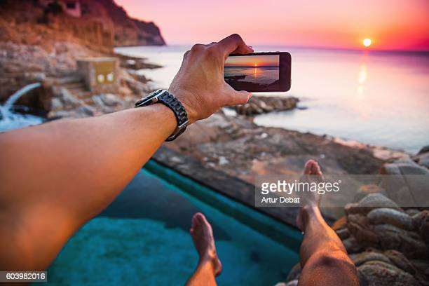 Guy from personal perspective taking pictures with smartphone from a natural pool in the Mediterranean Sea Costa Brava shoreline watching the sunrise with his legs levitating in the air during summer time.