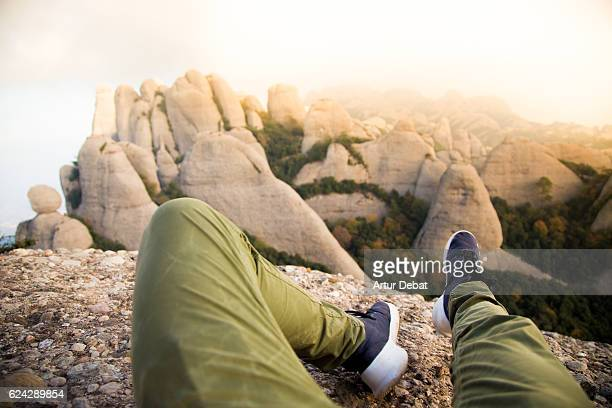 Guy from personal perspective with legs on top of summit in the Montserrat mountain with the stunning views on sunset light in the Catalonia region.