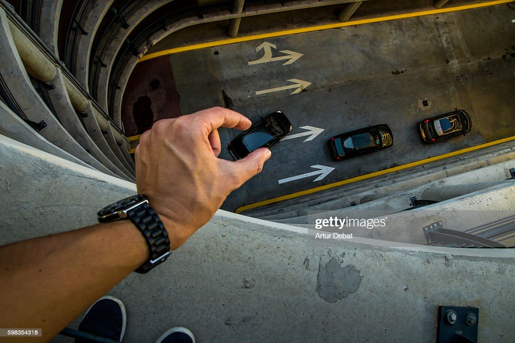Guy from personal point of view playing with perspective in a nice and creative view in a concrete parking garage holding little cars with his hands like toys. : Stock Photo