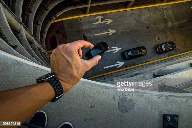 guy from personal point of view playing with perspective in a nice and creative view in a concrete parking garage holding little cars with his hands like toys. - human arm stock-fotos und bilder