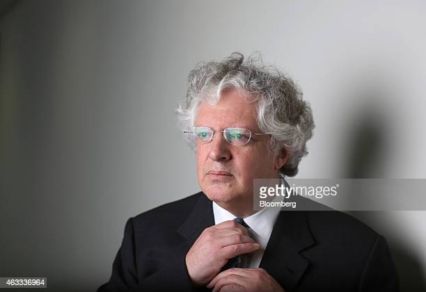 Guy Hands founder of Terra Firma Capital Partners adjusts his necktie as he poses for a photograph following a Bloomberg Television interview in...
