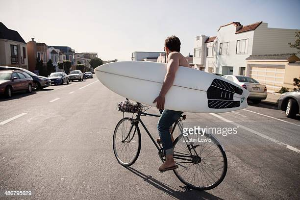 Guy holding a surf board riding a bike on street