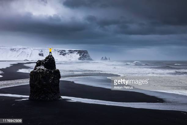 guy in a yellow jacket on top of a black rock - black sand stock pictures, royalty-free photos & images