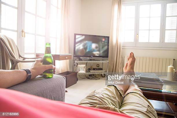 Guy in first person view on sofa with TV and beer.