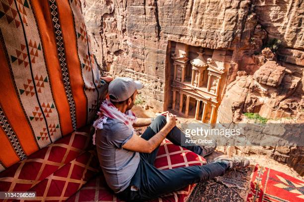 guy in the perfect place to contemplate the al-khazneh treasury tomb in the city of petra from above. - jordan middle east stock pictures, royalty-free photos & images