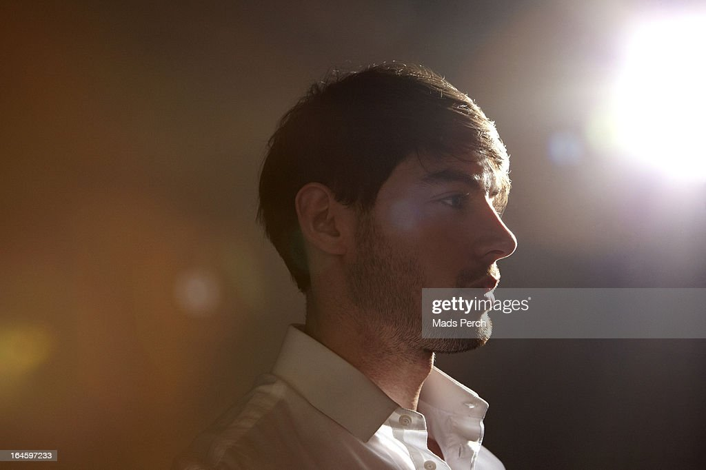 Guy In Venue With Flare Of Light Behind Him High-Res Stock ...