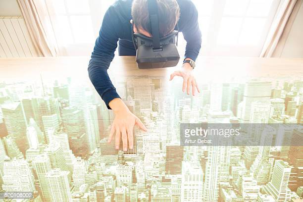 Guy interact with virtual reality headsets from the living room home touching and moving a hologram of a city view over the table.