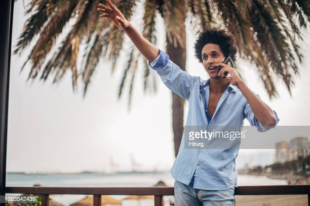 guy is talking on phone and waving - black hair stock pictures, royalty-free photos & images