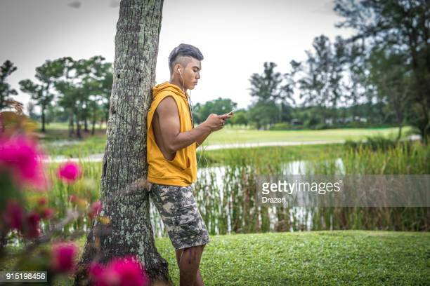 Guy is waiting for friends and listening to music in Southeast Asian country