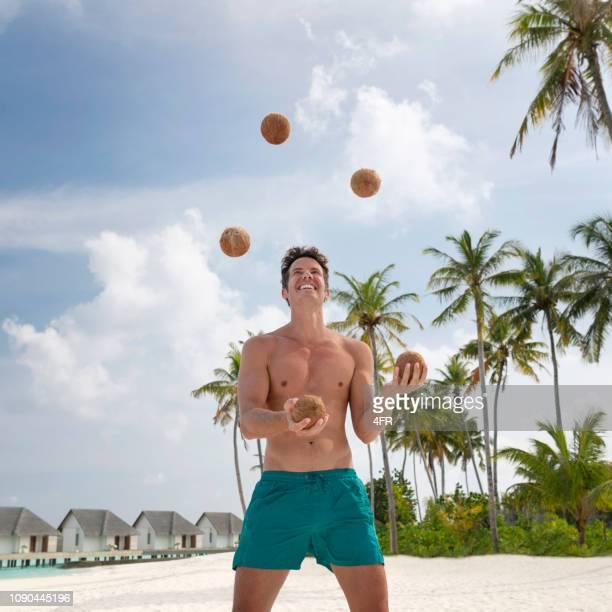 guy jongleren met kokosnoten, maldiven - jongleren stockfoto's en -beelden