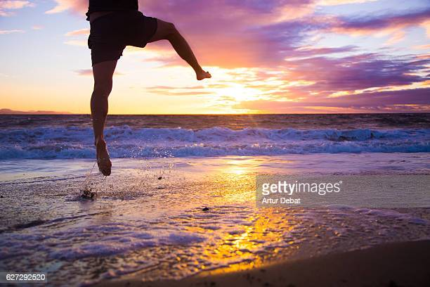 Guy jumping happy on the beach with nice sunset sky on the background during a nice travel through the volcanic island of Lanzarote.