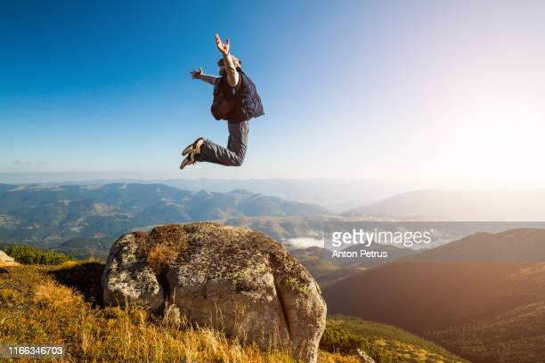 guy jumping in the mountains against the blue sky - extreme sports stock pictures, royalty-free photos & images