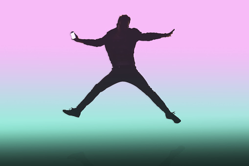 Guy jumping with mobile phone in colorful background. - gettyimageskorea