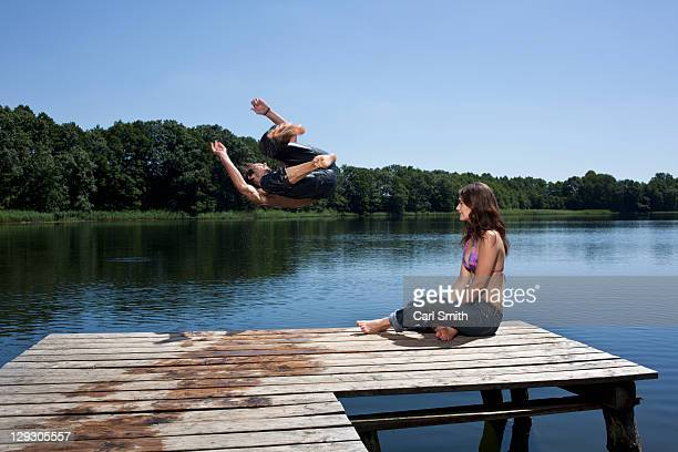 Guy jumps into lake with arms outstretched as girl watches on jetty