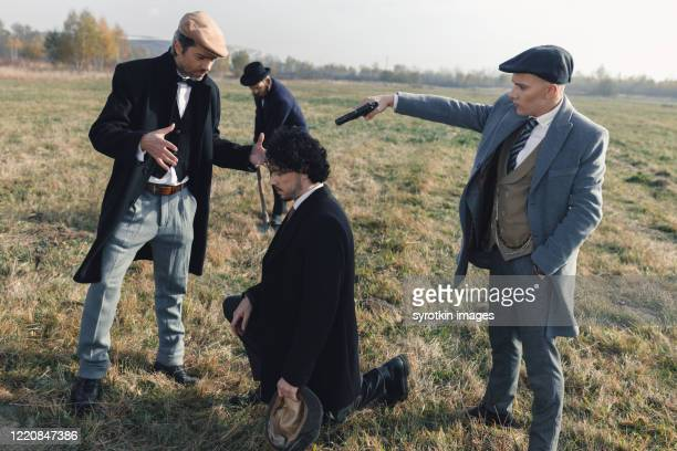 guy kneeling and looking down waiting for his death. - dead gangster stock pictures, royalty-free photos & images