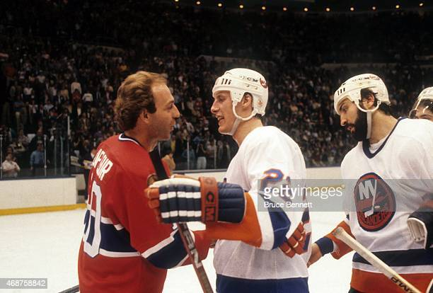 Guy Lafleur of the Montreal Canadiens shakes hands with Mike Bossy and John Tonelli of the New York Islanders after Game 6 of the 1984 Conference...