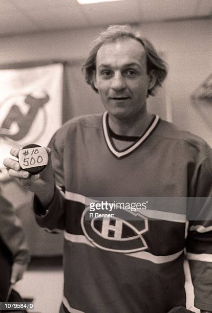 Guy Lafleur of the Montreal Canadiens shows the puck that he scored his 500th career goal with to the press after the game against the New Jersey...