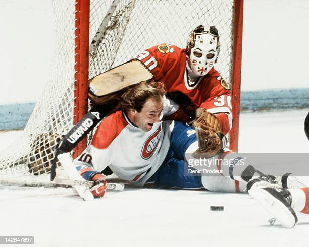 Guy Lafleur of the Montreal Canadiens slides into goalie Murray Bannerman of the Chicago Blackhawks while trying to control a loose puck near the net...