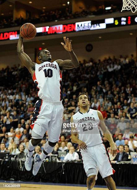 Guy Landry Edi of the Gonzaga Bulldogs goes in for a dunk against the Brigham Young Cougars in front of teammate Elias Harris during a semifinal game...