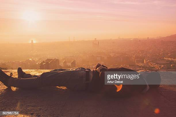 Guy laying contemplating from the Barcelona bunkers (Turo de la Rovira) the Barcelona cityscape on early morning.