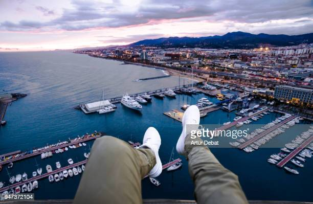 Guy legs from helicopter view with stunning harbor cityscape.
