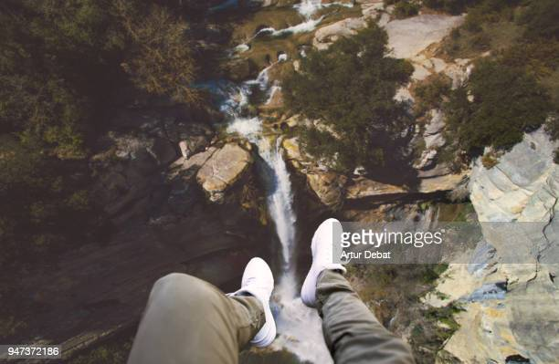 Guy legs from helicopter view with stunning waterfall landscape.